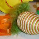 Plastično jajce ovito v 3 raznobarvne vrvice,okrašeno s svilenim trakom in perjem.