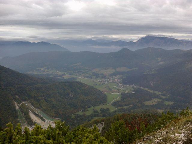 Pogled v dolino na smučarske skakalnice in Rateče ter Dobrač (v daljavi)