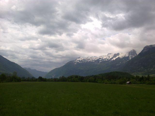 Razgled iz travnika na Kobariški Stol (levo v daljavi) in Kanin (desno)