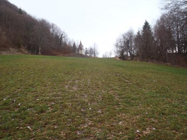 Samo ta travnik loči obeležje in cerkev.